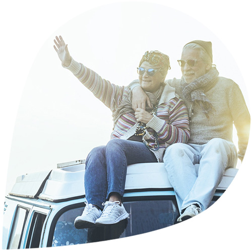 An older couple sitting on top of a van